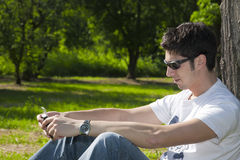 Young man relaxing in the park with his cell phone Stock Photos