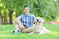 Young man relaxing in park seated with his dog royalty free stock images