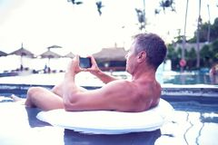 Young man relaxing on the pool, using mobile phone. Work and rel. Axation royalty free stock photo