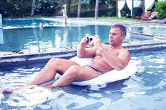 Young man relaxing on the pool, using mobile phone. Work and rel. Axation stock photos