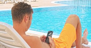Young man relaxing on the pool stock video footage