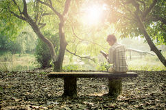 Young man relaxing & reading books alone Royalty Free Stock Image