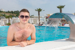 Young man relaxing in a resort swimming pool Royalty Free Stock Images