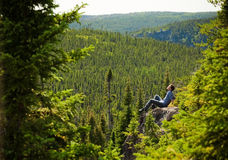 Young man on a rock in the middle of the nature Stock Image