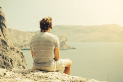 Young Man relaxing on rocky cliff  Sea and mountains on background. Lifestyle Summer vacations concept retro colors Royalty Free Stock Photos