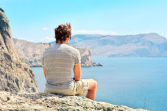 Young Man relaxing on rocky cliff sitting and looking on Sea Stock Image
