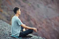 Young man relaxing on rocky cliff Royalty Free Stock Images