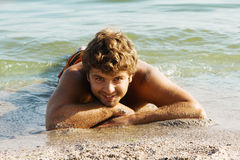 Young man relaxing on a sea shore Royalty Free Stock Photos