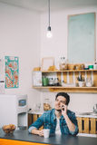 Young Man Relaxing Sitting In Kitchen Talking On Phone royalty free stock images