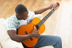 Young Man Relaxing Sitting On Sofa Playing Guitar Stock Photography