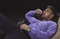 Young man relaxing on a sofa. Young busynessman in shirt having a rest on a leather sofa stock image