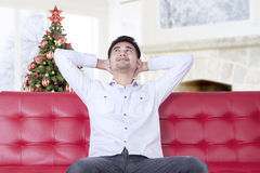 Young man relaxing on sofa with christmas tree Royalty Free Stock Photos