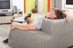 Young man relaxing on sofa Stock Photos