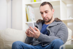 Young man relaxing on sofa and looking at his smart phone Royalty Free Stock Photography