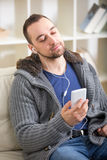 Young man relaxing on sofa and looking at his smart phone Royalty Free Stock Images