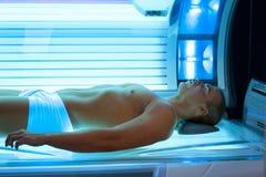 Young man relaxing during solarium treatment. Handsome young man relaxing during a tanning in a modern solarium Royalty Free Stock Photo