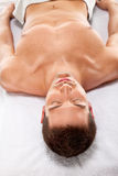 A young man is relaxing in spa center Stock Images