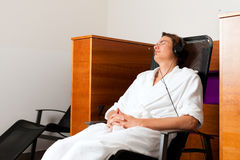 Young man relaxing in spa with music. Young man relaxing in spa hearing music with headset in quiet room stock images