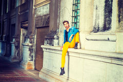 Young Man relaxing on street. Worker Relaxing Outside. Dressing in a blue jacket with hood, black underwear, yellow pants, leather boot shoes, a young handsome Stock Images
