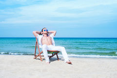 Young man relaxing on a sunbed on the beach Royalty Free Stock Image