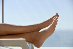 Young man relaxing in a sunlounger. Closeup of the feet and legs of a caucasian man relaxing lying down on a sunlounger in a terrace Stock Photo
