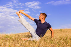 Young man relaxing on the sunny meadow. Stock Photos