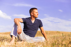 Young man relaxing on the sunny meadow. Royalty Free Stock Photo