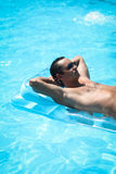 Young man relaxing in the swimming pool Stock Photo