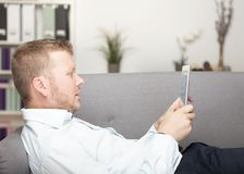 Young man relaxing with a tablet computer stock photography