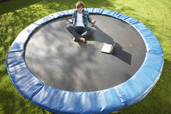 Young Man Relaxing On Trampoline With Laptop Stock Photography