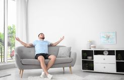 Young man relaxing under air conditioner. At home royalty free stock image