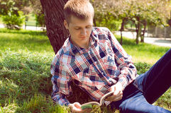 A young man relaxing under a tree, reading a book. Outdoor shot Royalty Free Stock Images