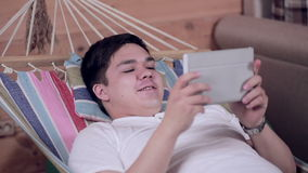 Young man relaxing using tablet computer touchscreen in hammock. HD stock video footage