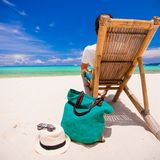 Young man relaxing in wooden chair on white sandy Stock Photo