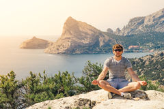 Young Man relaxing yoga on rocky mountains Stock Image