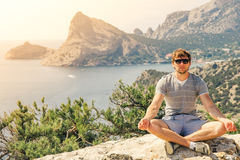 Young Man relaxing yoga on rocky mountains Royalty Free Stock Photography