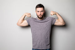 Young man with relief muscles in jeans in shirt on a gray background Stock Photo