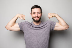 Young man with relief muscles in jeans in shirt on a gray background Royalty Free Stock Images