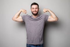 Young man with relief muscles in jeans in shirt on a gray background Stock Photos