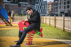 Young man reliving his childhood plying in a children's playground Stock Photos