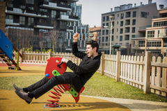 Young man reliving his childhood plying in a. Children's playground riding on a colorful red spring seat with a happy smile in an urban park Royalty Free Stock Photo