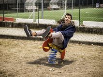 Young man reliving his childhood. Plying in a children`s playground riding on a colorful red spring seat with a happy smile in an urban park Stock Image
