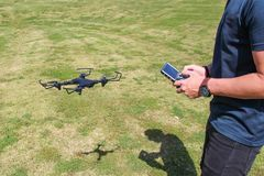 Young man with remote control cell phone flying drone. Sunny green nature royalty free stock images