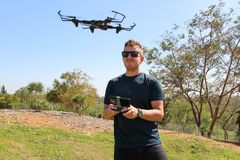 Young man with remote control cell phone flying drone. Sunny green nature royalty free stock photography