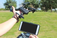 Young man with remote control cell phone hold drone. Sunny green royalty free stock images