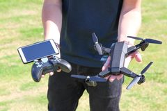 Young man with remote control cell phone hold drone. Sunny green stock image