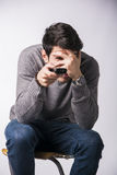 Young man with remote control, covering his eyes scared Royalty Free Stock Photography