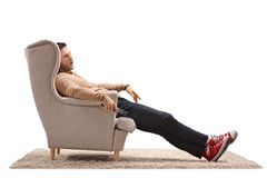 Young man with a remote control sleeping in an armchair stock image