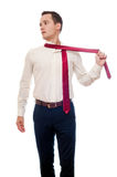 Young man removes a suit isolated on white. Businessman or student untie a tie. Groom after weeding. Office worker after work. royalty free stock photography