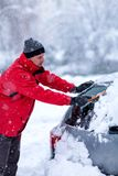 Man removing snow from car. Man cleaning snow from car windshield with brush, close up. Snowy winter weather. Car in snow after stock photo